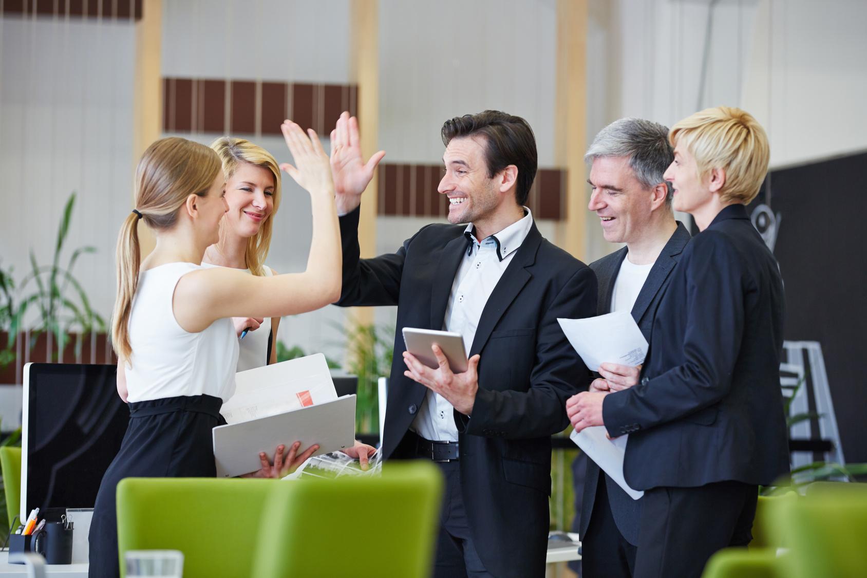 Erfolgreiche Geschäftsleute geben sich lachend High Five im Büro